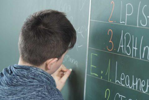 Ein Schüler schreibt etwas an die Tafel