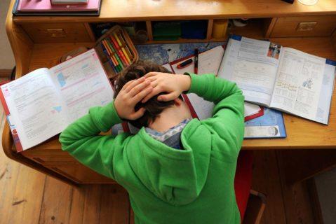 Ein Schüler verzewifelt über seinen Hausaufgaben.