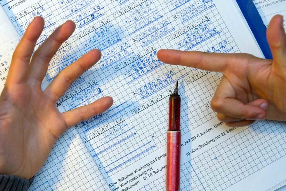 Ein Kind löst Matheaufgaben mit Fingern