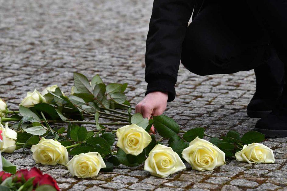 Eine Person legt weiße Rosen nieder