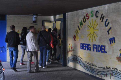 Eine Gruppe von Erwachsenen betritt im Rahmen der Lernreise die Primusschule Berg Fidel Münster