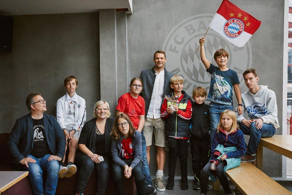 Acht Kinder und zwei Erwachsene der Martinschule Greifswals posieren mit Manuel Neuer für ein Gruppenbild