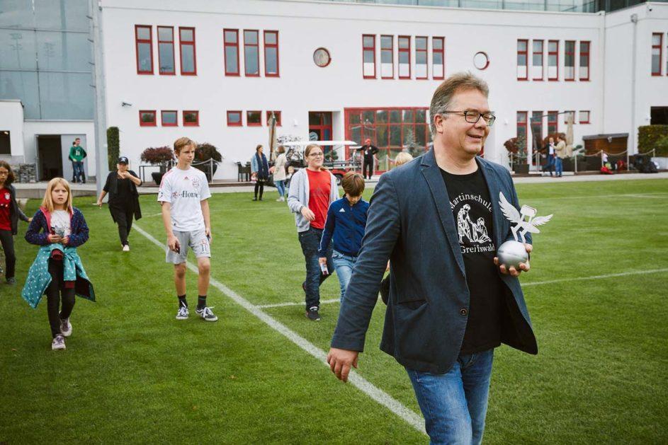 Ein Mann und Kinder der Martinschule Greifswald gehen über einen Fußballplatz