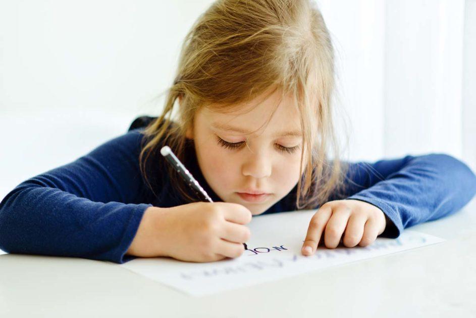 Eine junge Schülerin schreibt mit einem schwarzem Filzstift