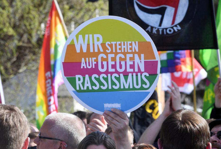 """ARCHIV - 07.04.2018, Rheinland-Pfalz, Kandel: Teilnehmer der Demonstration """"M‰nnerb¸ndnis Kandel"""", die dem linken Lager zugerechnet werden, demonstrieren unter dem Motto """"B¸rgerrechte statt rechte B¸rger"""". Es wird dabei ein Plakat in die Hˆhe gehalten auf dem steht """"Wir stehen auf gegen Rassismus"""". (zu dpa ´Zwei Demonstrationen in Kandel kurz vor Urteil in Mordprozessª vom 01.09.2018) Foto: Uli Deck/dpa +++ dpa-Bildfunk +++"""