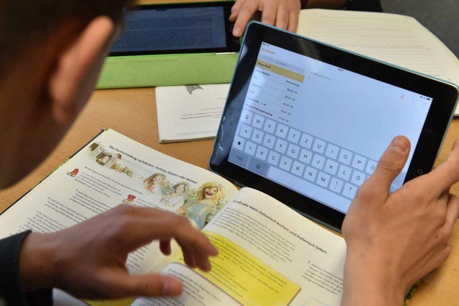 Ein Schüler arbeitet mit eine Tablet