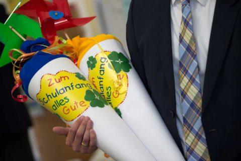 Ein Schulanfänger hält zwei Zuckertüten