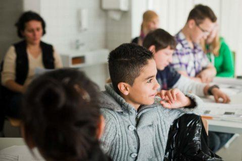 Kinder sitzen an Tischen im Klassenzimmer und arbeiten
