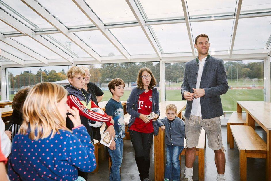 Kinder der Martinschule und Manuel Neuer stehen vor Tischen und Bänken