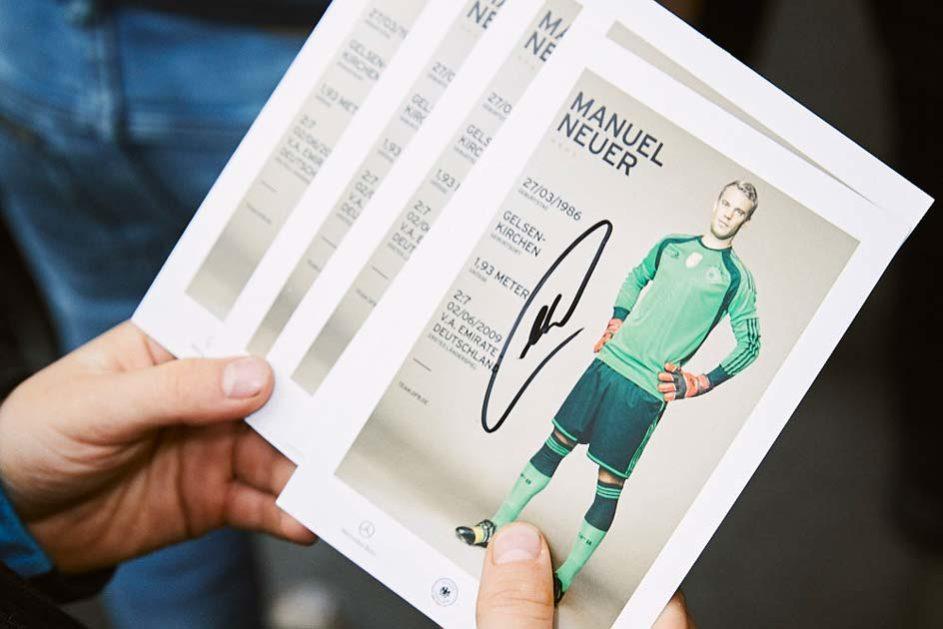 Ein Kind der Martinschule Greifswald hält eine Autogrammkarte mit dem Bild und der Unterschrift von Manuel Neuer