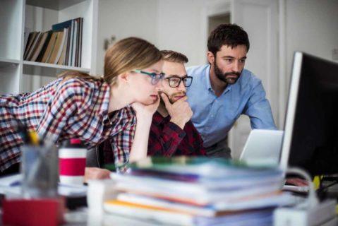 Drei Lehrer schuaen auf einen Computerbildschirm