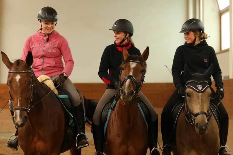 drei Mädchen sitzen jeweils auf einem Pferd