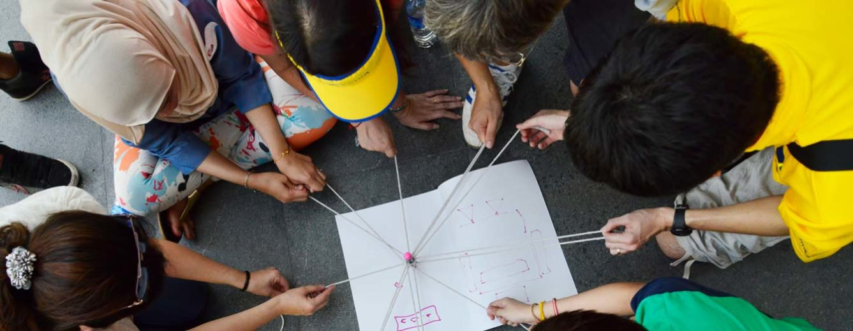 Kinder aus Singapur beugen sich in der Schule über ein Arbeitsblatt