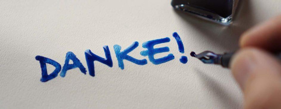 Zum Weltlehrertag schreibt jemand mit blauer Tinte das Wort Danke
