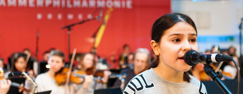 Eine Schülerin singt am Mikrophon, im Hintergrund ein Schülerorchester