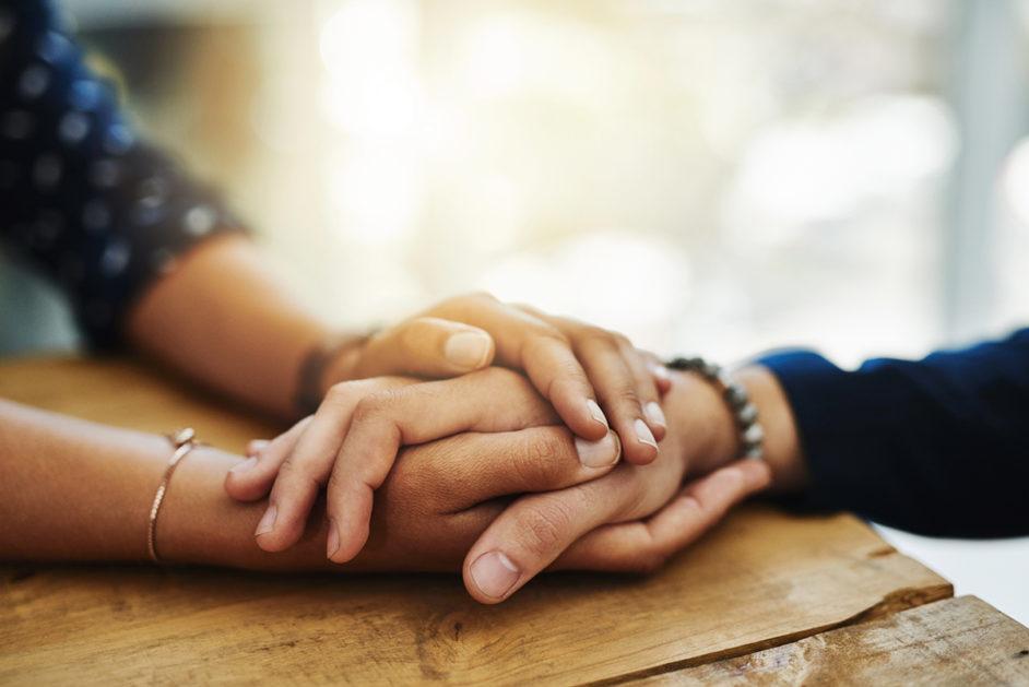 Trost bei sexueller Gewalt: Eine Person umschließt mit ihren Händen die Hände einer anderen Person