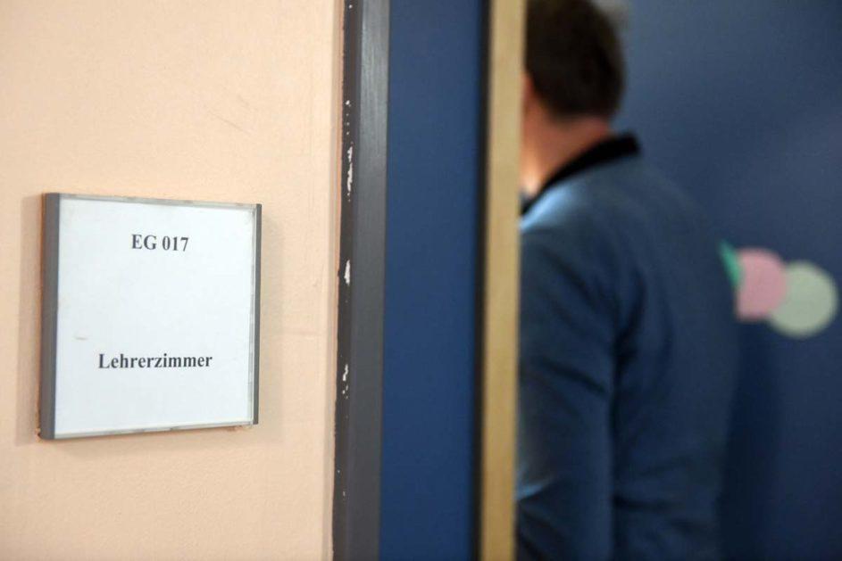Ein Mann geht an einem Schild vorbei, das den Weg zum Lehrerzimmer weist.