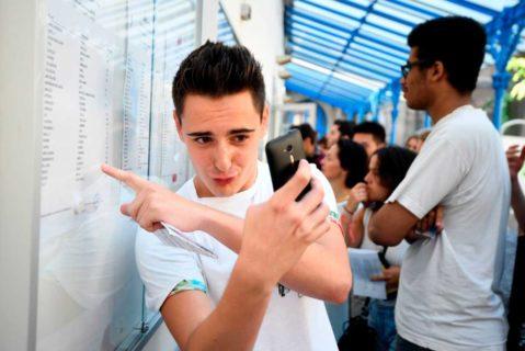 Ein Schüler in Paris macht ein Selfie von sich und seinen Prüfungsergebnissen.