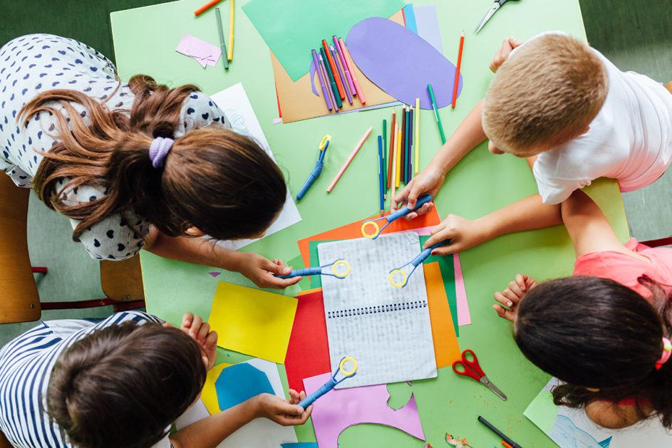 Kinder beugen sich gemeinsam über ein Heft und Bastelmaterial