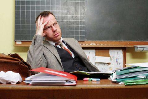 Lehrer korrigiert Klausuren