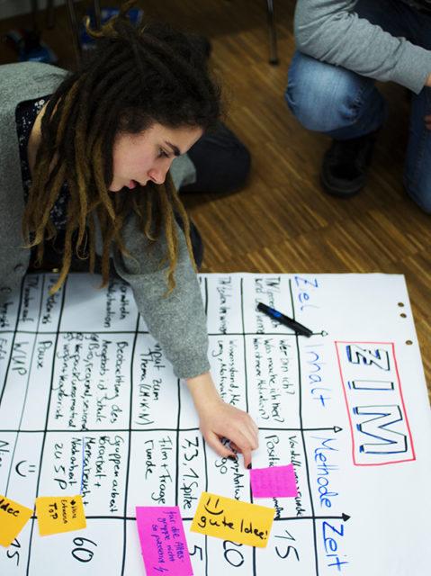 Eine junge Frau schreibt beim Klima-Workshop auf ein großes Plakat