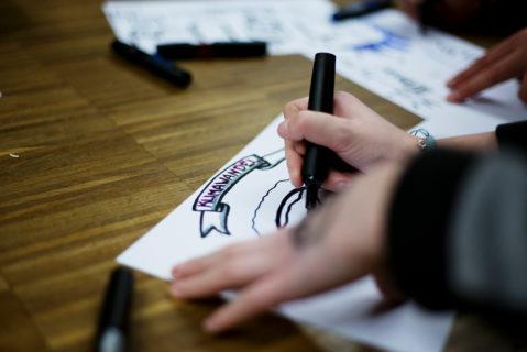Eine Klima-Botschafterin hält einen Stift und schreibt das Wort Klimawandel