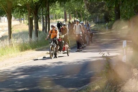 Mehrere Kinder fahren für das Projekt Herausforderung mit dem Rad oder mit einem Longboard eine Straße entlang