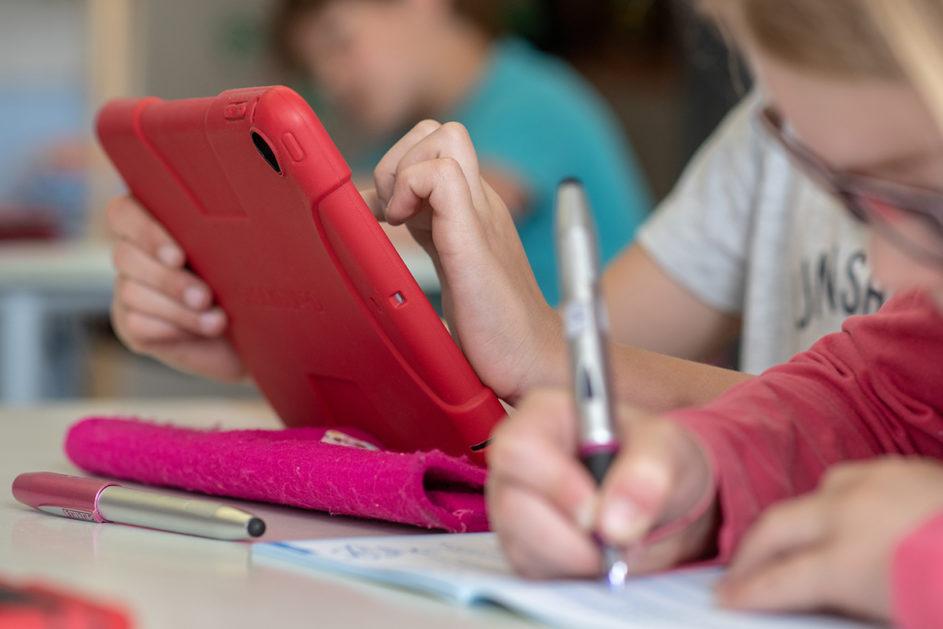 Grundschüler nutzen ein Tablet.