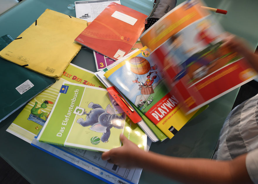 Stichwort Bildungsarmut: ein Kind hält mehrere Schulhefte und Schulbücher in der Hand