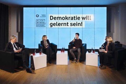 Podiumsdiskussion mit vier Diskutanten vor einer Wand mit dem Schriftzug Demokratie will gelernt sein.
