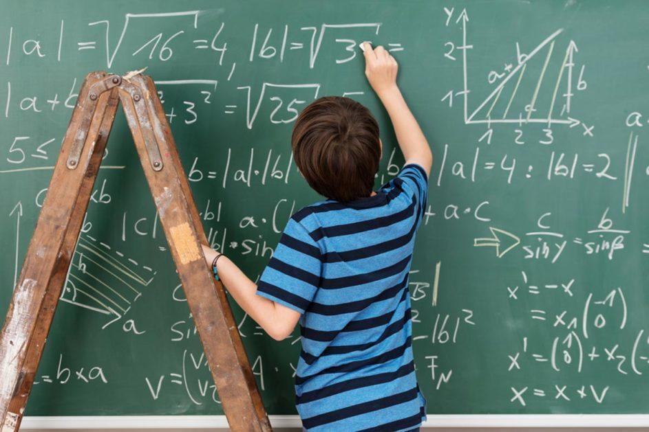 Ein Junge schreibt eine Gleichung an eine Tafel