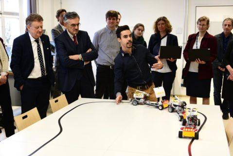 Lehramtsstudent Fabio Bove zeigt mit Spielzeug-Lastern, wie autonomes Fahren im Konvoi funktionieren kann.