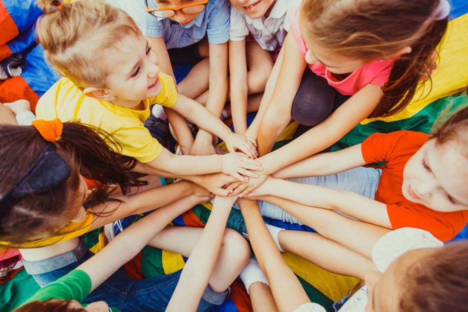 Kinder legen die Hände aufeinander