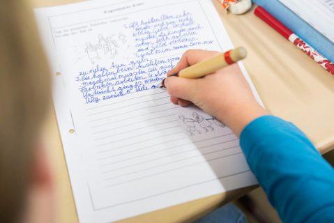 Ein Schüler schreibt in sein Schreibheft