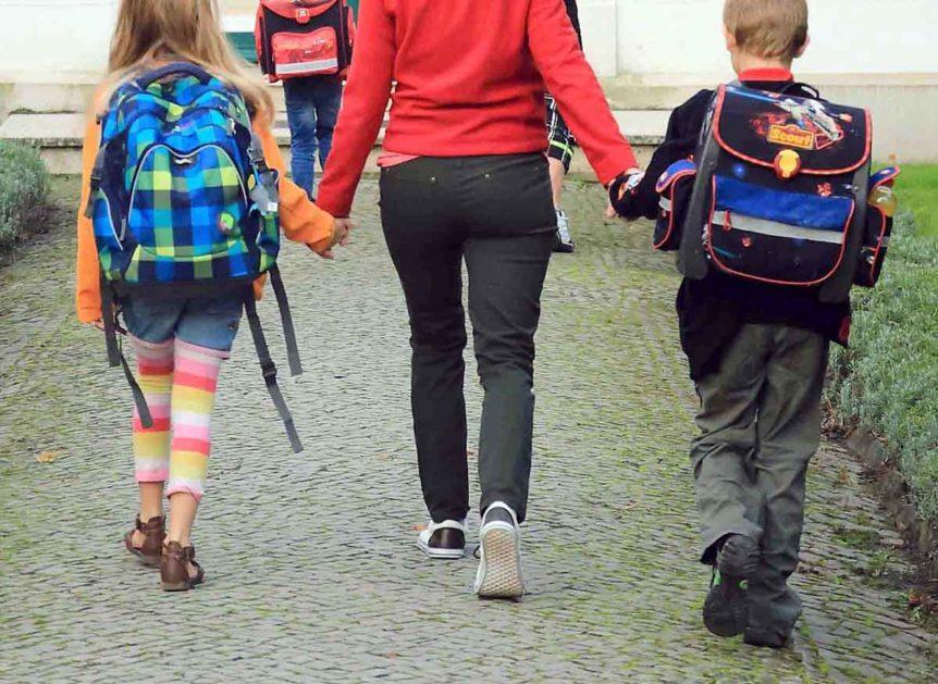 Eine Mutter hat zwei Schulkinder an den Händen