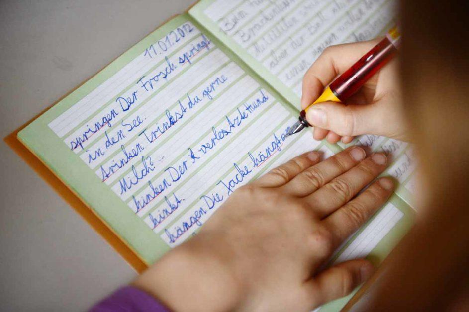 Ein achtjähriges Mädchen übt in ihrem Schreibheft die deutsche Rechtschreibung.