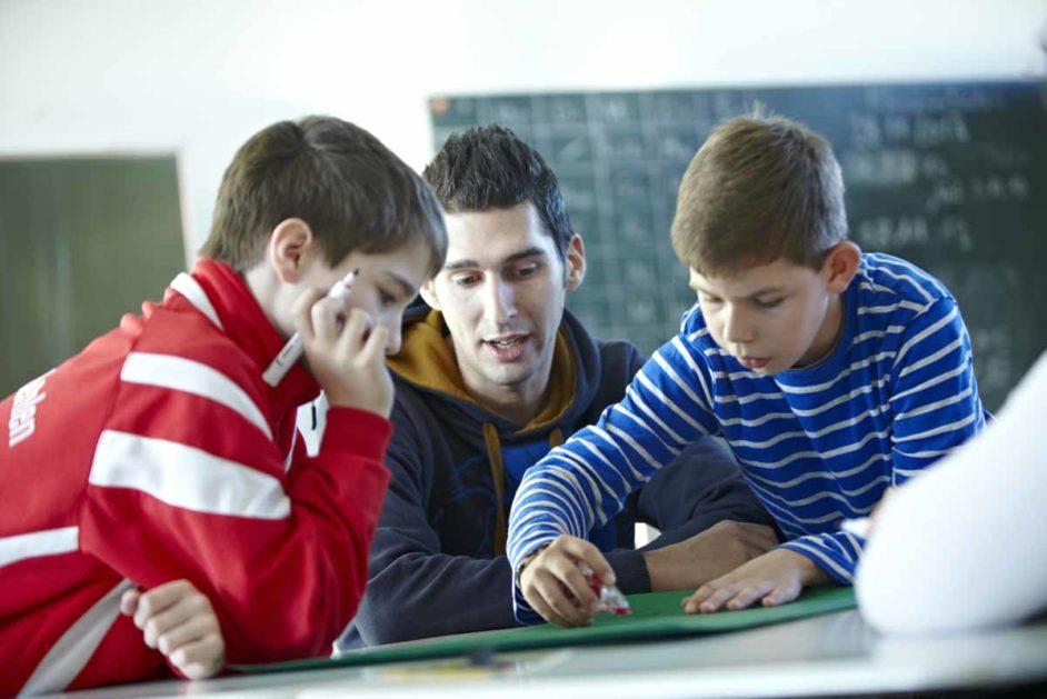 Zwei Schüler arbeiten mit einem Pädagogen an einer Präsentation