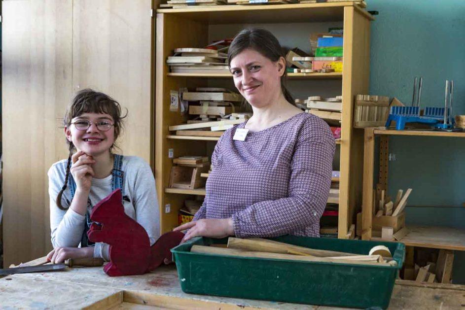 Kind und Lehrerin an der Werkbank