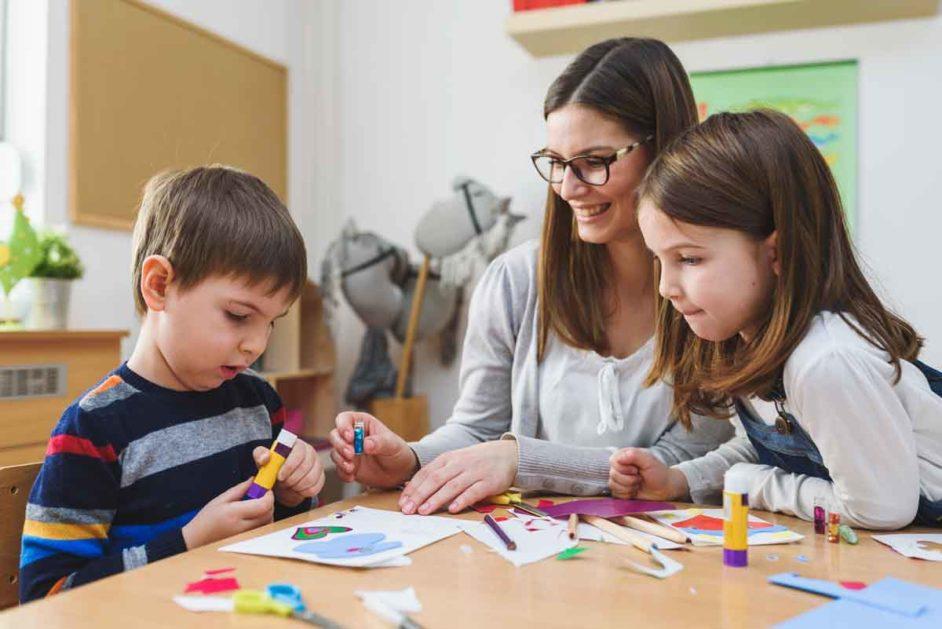 Kinder sitzen mit Lehrerin am Tisch beim Basteln