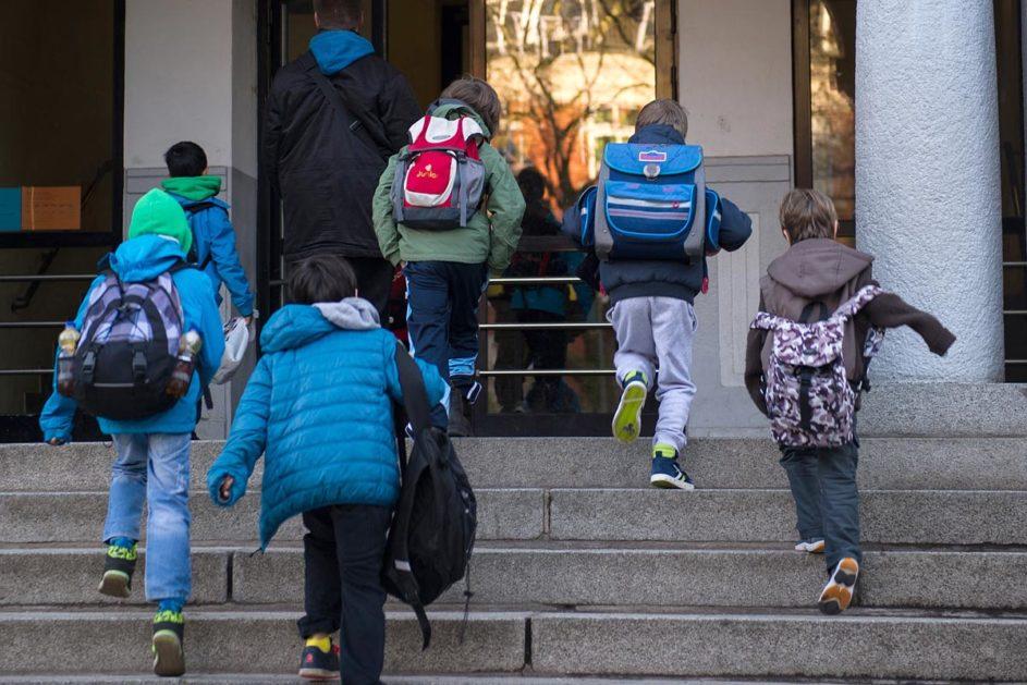 Schüler laufen Treppe zur Schule hoch