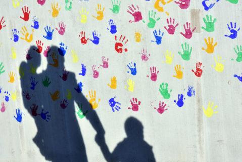 Der Schatten eines Vaters mit zwei Kindern an der Hand