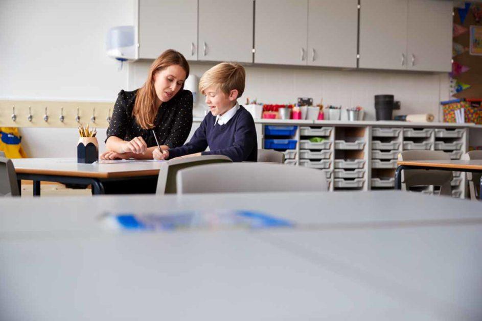 Lehrerin arbeitet mit einem Schüler am Tisch