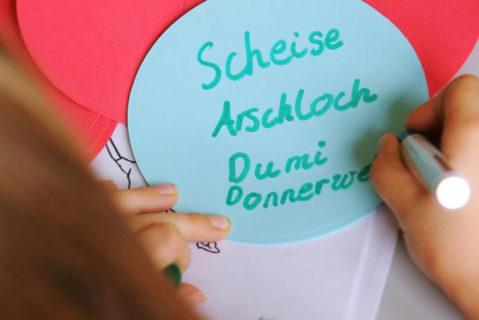 Eine Schülerin schreibt Schimpfwörter auf