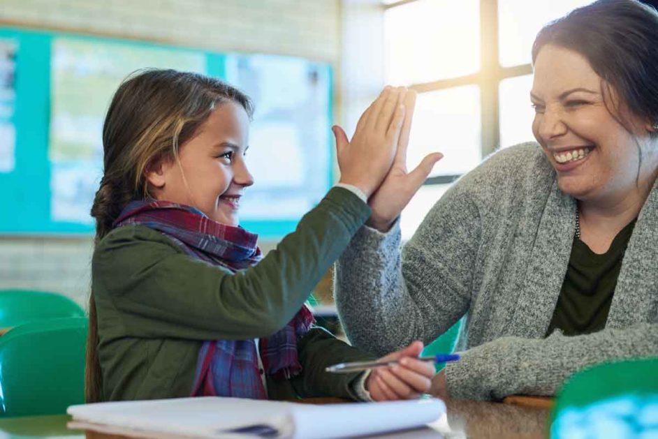 Lehrerin klatscht mit einer Schülerin ab