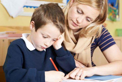 Lehrerin hilft einem Schüler bei einer Aufgabe
