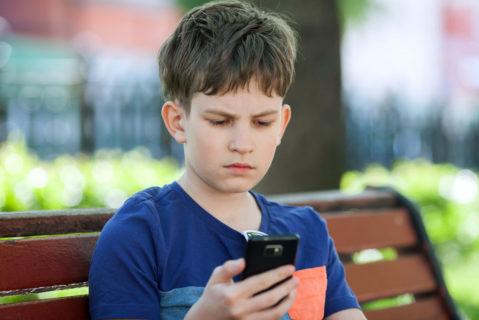 Schüler sitzt auf Bank und liest auf dem Handy