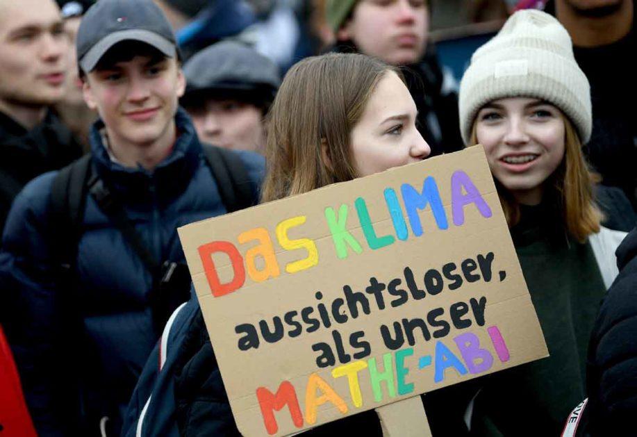 """Schüler protestieren mit einem Schild mit der Aufschrift """" Das Klima aussichtsloser als unser Mathe-Abi"""""""