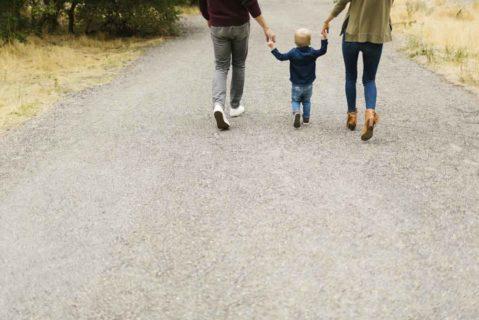 Eltern gehen mit Kind auf einem Weg spazieren