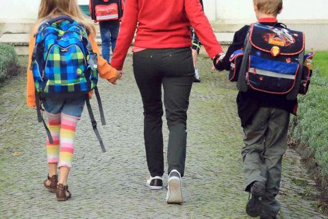 Eine Mutter hält ihre beiden Kinder an der Hand