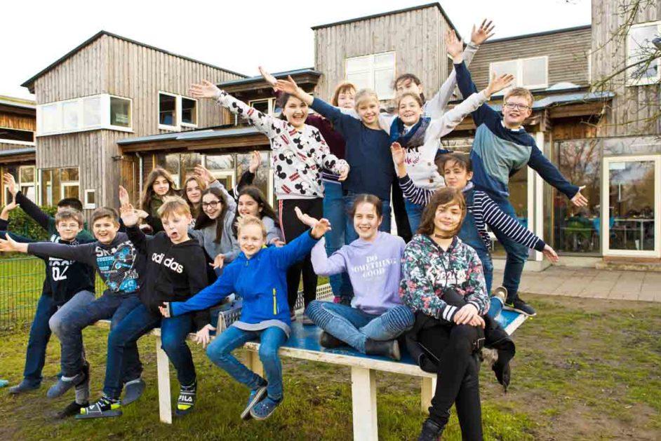 Schülerinnen und Schüler posieren auf der Tischtennisplatte vor dem Schulgebäude